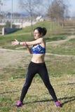 De vrouw voert zich het uitrekken vóór het aanstoten in een park uit stock foto's