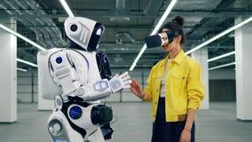 De vrouw in VR-glazen raakt de hand van de witte robot stock video