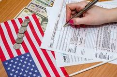 De vrouw vult belastingsvorm 1040 met geld, pen, vlag van de V.S. en calculator Stock Foto