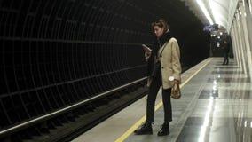 de vrouw wacht op een trein in de metro stock videobeelden