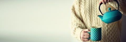 De vrouw in warme gebreide wollen sweater houdt turkooise theepot en gietend aftreksel in met de hand gemaakte kop De ruimte van  Royalty-vrije Stock Afbeelding