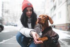 De vrouw in warme kleren zit op de grond met een puppy op de achtergrond van de straat in de wintertijd stock afbeeldingen