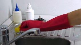 De vrouw wast een metaalgootsteen met spons in de keuken in rode handschoenen Het proces van spijkers stock video