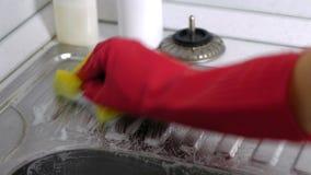 De vrouw wast een metaalgootsteen met spons in de keuken in rode handschoenen Het proces van spijkers stock footage