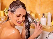 De vrouw wast haar hoofd bij badkamers Royalty-vrije Stock Afbeelding
