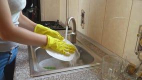 De vrouw wast schotels stock video