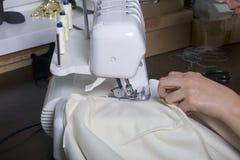 De vrouw werkt aan het product op overlock Overlock met witte draad De vrouw leidt de doek in de klauw o wordt vastgeklemd dat Royalty-vrije Stock Afbeeldingen