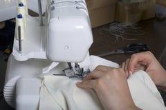De vrouw werkt aan het product op overlock Overlock met witte draad De vrouw leidt de doek in de klauw o wordt vastgeklemd dat Stock Fotografie