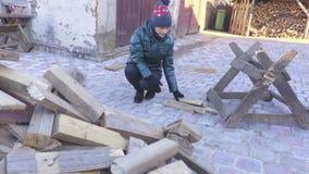 De vrouw werpt brandhout in stapel stock videobeelden