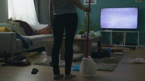 De vrouw werpt emmer en de zwabber wegens knoeit in woonkamer na partij stock videobeelden