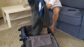 De vrouw werpt haar dingen van echtgenootalcoholisten in een koffer scheidingsclose-up stock videobeelden