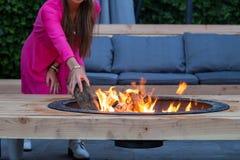 De vrouw werpt het programma opent brandkuil in de tuin op een de zomerdag royalty-vrije stock foto