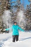 De vrouw werpt op sneeuw in het de winterbos Stock Fotografie