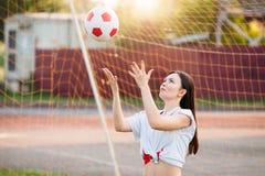 De vrouw werpt voetbalbal bij stadion op achtergrond van net van voetbaldoelstellingen stock afbeelding