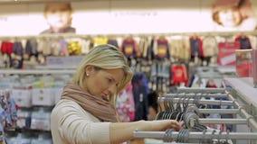 De vrouw in winkel, kiest kleren stock videobeelden