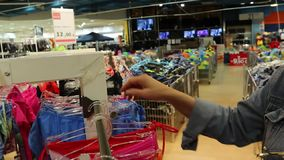 De vrouw in winkel kiest zwempak stock footage