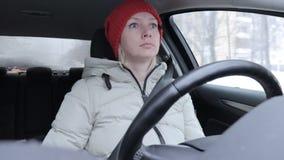 De vrouw in de winterkleren en de sinaasappel breiden hoed die een auto op de winterweg drijven stock footage