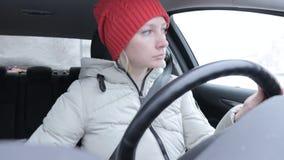 De vrouw in de winterkleren en de sinaasappel breiden hoed die een auto op de winterweg drijven stock videobeelden