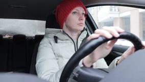 De vrouw in de winterkleren en de sinaasappel breiden hoed die een auto op de winterweg drijven stock video