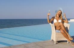 De vrouw in witte bikini ontspant dichtbij oneindigheidspool Stock Foto's