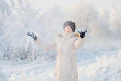 De vrouw in witte laag, werpt sneeuw Royalty-vrije Stock Fotografie