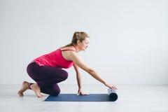 De vrouw in witte ruimte spreidt een yogamat uit royalty-vrije stock fotografie