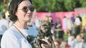 De vrouw woont het openluchtfestival met haar klein ras van hondchihuahua bij stock videobeelden