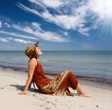 De vrouw wordt gebruind op zee strand stock fotografie