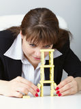De vrouw wordt geconcentreerd om een toren met domino te bouwen Stock Afbeeldingen