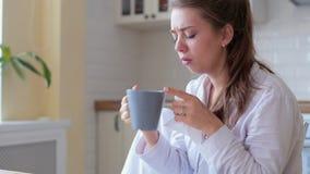 De vrouw wordt koud en hoest zij het drinken hete citroenthee om haar gevoel in de woonkamer beter te laten thuis stock video