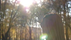 De vrouw wordt verblind door de heldere de herfstzon Het meisje bekijkt de zon door de vingers van zijn hand 4k langzame 60fps stock video