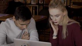 De vrouw wordt verrast door vrouw naast de mens na het lezen van nieuws en bevorderingen stock video