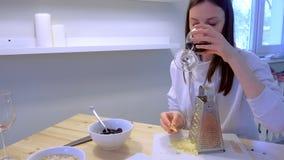 De vrouw wrijft kaas thuis op rasp en drinkt rode wijn in de keuken Het paar kookt diner stock footage