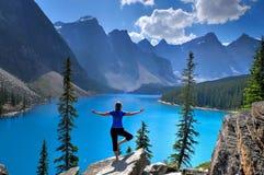 De vrouw in yoga stelt bij alpiene meer en bergen stock foto's