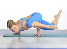 De vrouw in yoga stelt status op haar handen Stock Afbeelding
