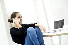 De vrouw zat terloops als voorzitter die op telefoon spreken Stock Afbeelding