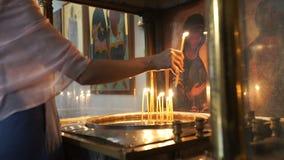 De vrouw zet een kaars dichtbij het pictogram in klooster stock video