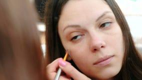 De vrouw zet een Stichtings toon- room op het gezicht gebruikend een borstel voor de spiegel Het gezichts vooraanzicht van de clo stock video