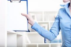 De vrouw zet een tablet met documenten in een Shelfs Stock Foto's