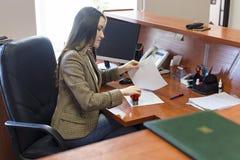 De vrouw zet een zegel aan het document op de Desktop Het werk in het bureau royalty-vrije stock afbeeldingen