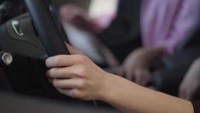 De vrouw zet haar handen op grote stuurwiel dichte omhooggaand Modern meisje die auto in motorshow kiezen Concept het kopen stock video