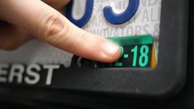 De vrouw zet nieuwe vervaldatumsticker op nummerplaat stock footage