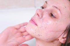 De vrouw zet schrobt op het gezicht die in de badkamers liggen De close-up van het gezicht Witte achtergrond royalty-vrije stock foto's