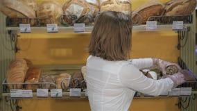 De vrouw zet zwart brood op het rek stock footage