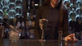 De vrouw zette bovenop kommetaal sauser met stukken van kaas, droge rozen en framboos Metaalkop met drank op de bar stock videobeelden