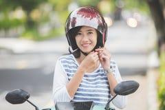 De vrouw zette haar helm aan alvorens een motor te berijden stock afbeelding