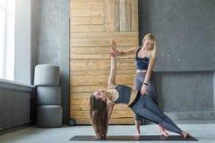 De vrouw in zijplank stelt met trainer bij yogaklasse stock fotografie