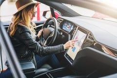 De vrouw zit achter wiel in auto en gebruikt elektronisch dashboard Meisjesreiziger die manier zoeken door navigatiesysteem stock afbeelding
