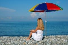 De vrouw zit bij kust onder paraplu Royalty-vrije Stock Foto