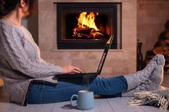 De vrouw zit bij de vloer met laptop op de open haardachtergrond stock afbeelding